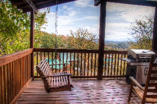 Main level deck, with tables, chairs, swing & gas grill